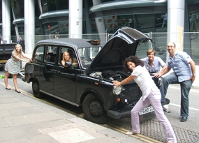A group of people leaning of a black cab during a GPS treasure hunt