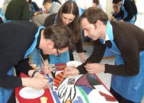A team of people painting a colourful picture during a creative indoor team building activity