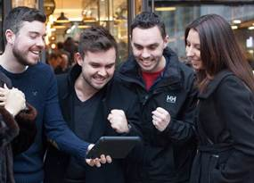 A team gathered around a tablet completing a GPS Treasure hunt