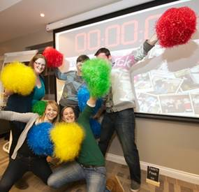 A group of 5 people with Pom Poms taking part in team building activities for large groups.