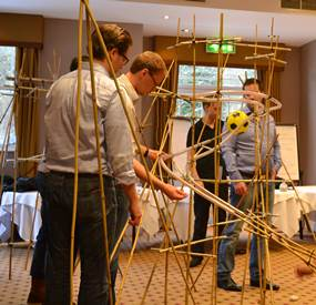 A team completing some Indoor team building activities for large groups where they need to build a rollercoaster out of the materials provided.