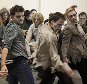 A group of people dressed up as zombies and performing the Thriller dance and taking part in team building activities for a large groups
