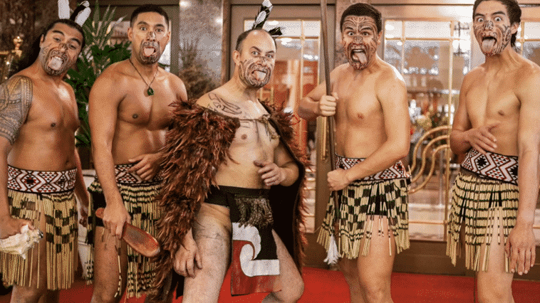 Five Maori masters performing the Haka dressed in traditional outfits