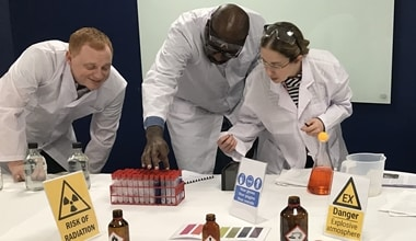 A group of three people wearing white lab coats looking for clues in a mock laboratory during an 'escape room' indoor team building activity.