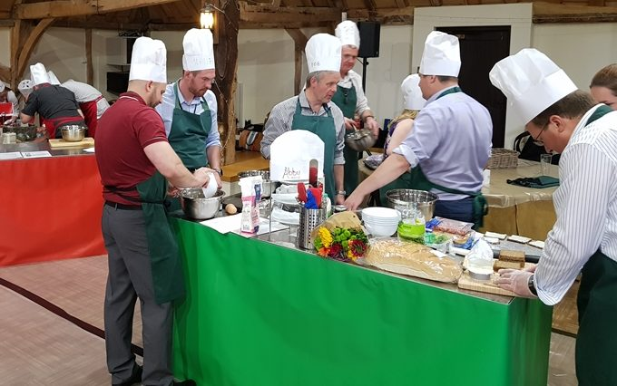 A team discussing their strategy during a baking team building event.