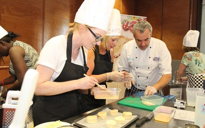Two team members eggwash their scones during a baking team building event.