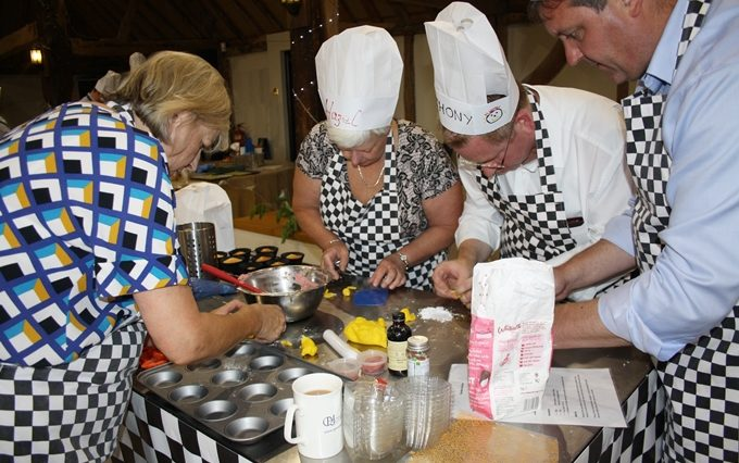 Four team members focus on finishing their baked items during a baking team building event.
