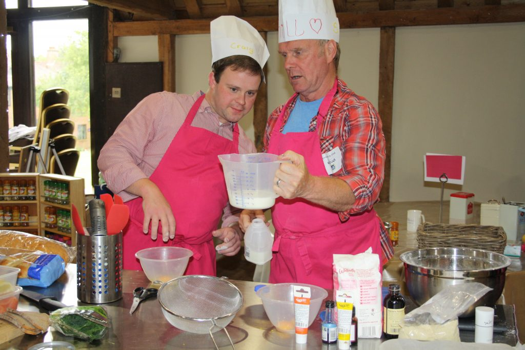 Two men measuring out ingrediants during a Big bake corporate team building event