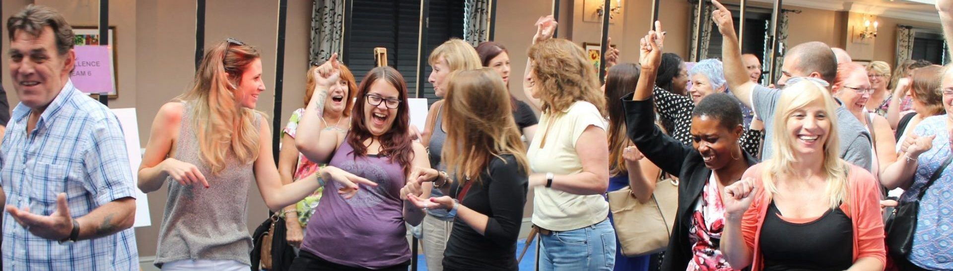 A group of people laughing and waving thier arms whilst taking part in an indoor team building activity