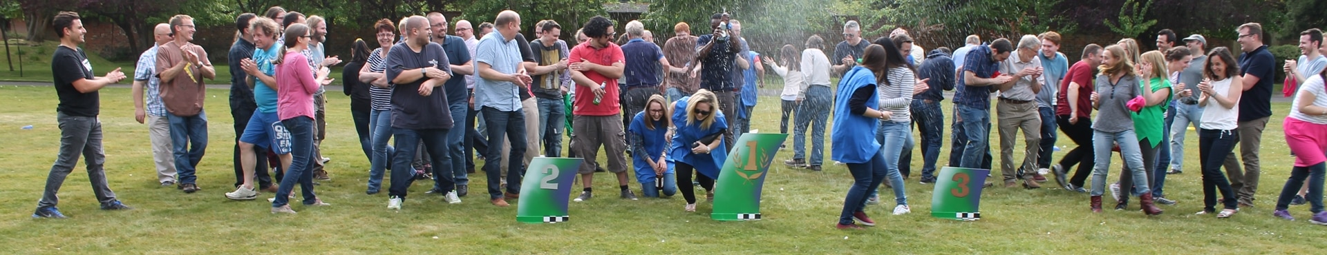 A group of people spraying champagne and celebrating winning an outdoor team building activity