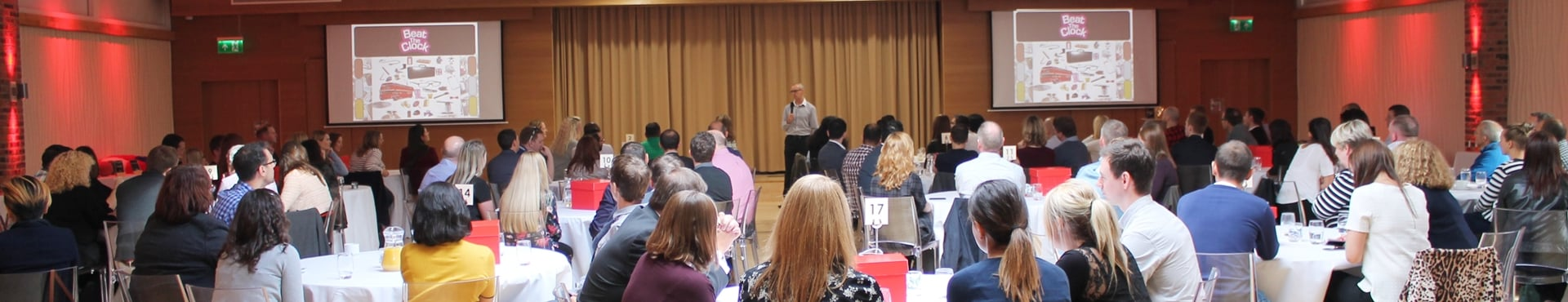 A large group of people at a corporate away day, all litening to a speaker at the front of a confenrece room.