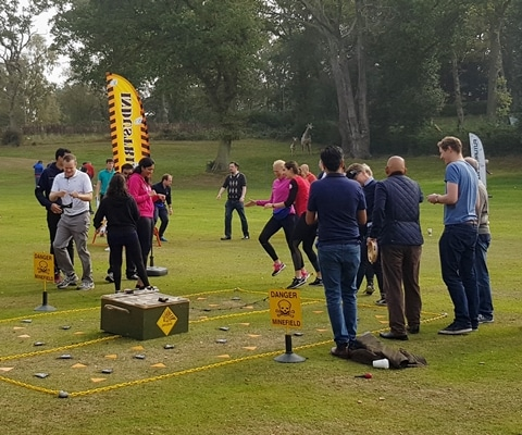A group of people taking part in a team building activity outside.