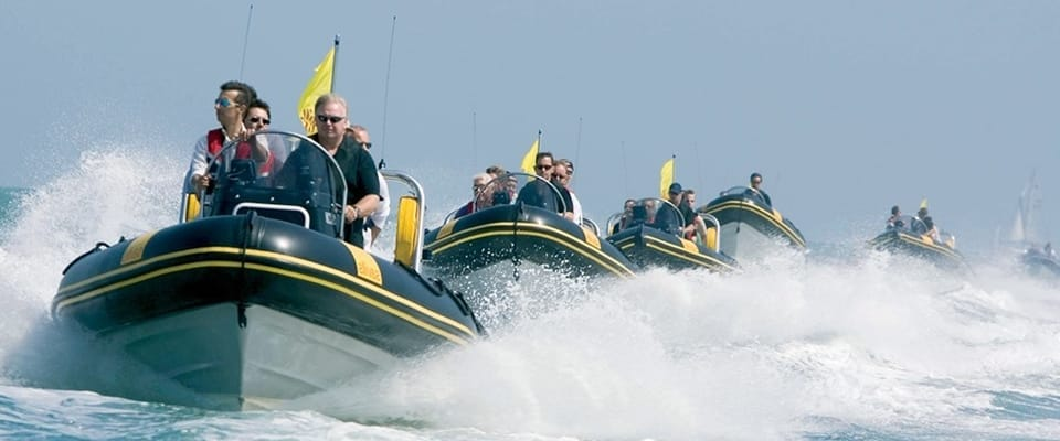 Five Rigid Inflatable Boats on the sea in a line with passengers in them.