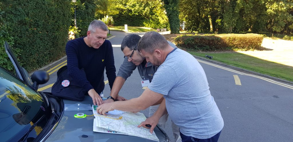 A team looking at a map and discussing ideas during an italian job corporate team building event