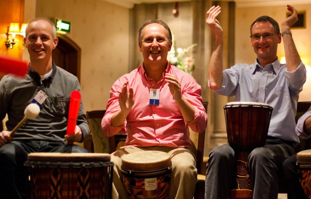 Thre people playing the drums during a drum beats team building event