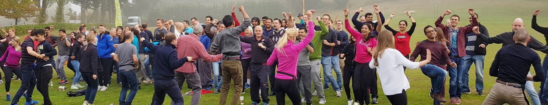 A group of people dancing around with their arms in the air before a team building activity