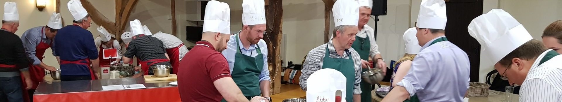 A group of people wearing paper chefs hats and taking part in a cookery team building activity