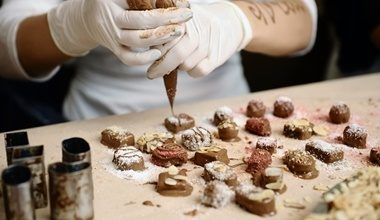 A chef making hand made chocolates with a piping bag.