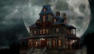 A spooky old house at night set against a giant full moon